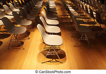 several rows of white plastic chairs with chromium-plated...