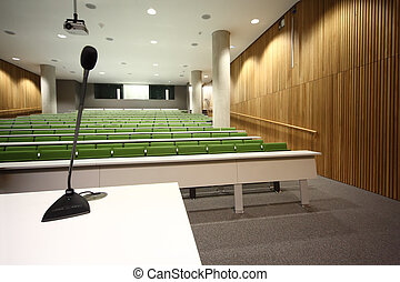 large auditorium with rows of green seats and white tables, focus on first row