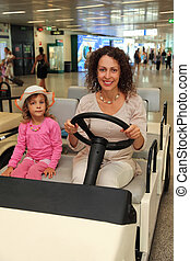 young mother and little daughter riding on electric car in airport
