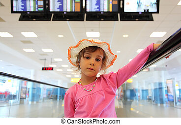 beautiful little girl in hat and pink blouse rides on escalator, schedule on displays