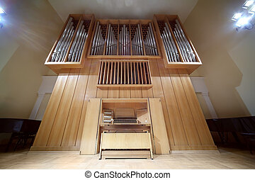 Massive wooden pipe organ with long metal tubes; control...