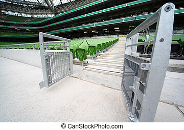Rows of folded, green, plastic seats in very big, empty stadium, entrance on tribunes