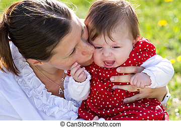 mother kissing baby in the park