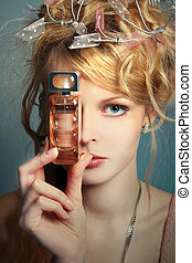 beautiful girl with a bottle of perfume about her face -...