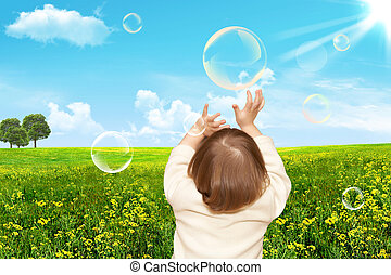 The small girl plays with soap bubbles Nature