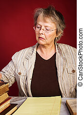 Preparing for lesson - Mature woman with old books takes...