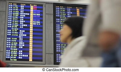 Airport Flight Departure Board - People walk past a flight...