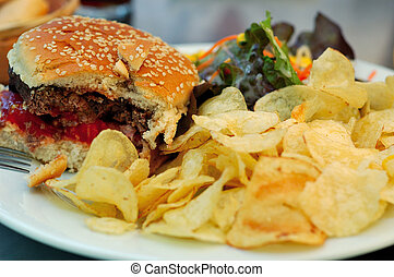 Incomplete burger with chips and salad
