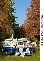 Camping time - Old style camper with two chairs next to it