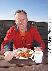 Traditional English Breakfast - Man eating a traditional...