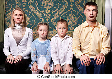 Family portrait - A young family sitting in row and looking...
