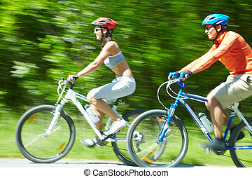 Speed - Image in motion of two bicyclists riding on country...