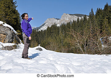 Alone trekking woman in the snowy mountains in the Carpathians, Romania