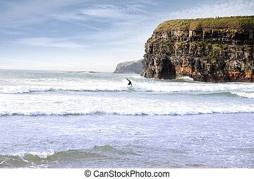 lone surfer near cliffs - beautiful clean atlantic ocean...
