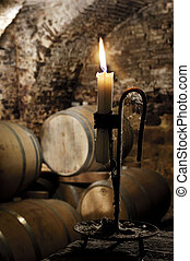 Old candle in a wine barrel cellar - Old candlestick with...