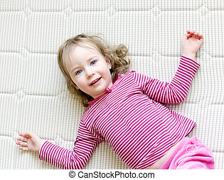 Cute little girl lying on a mattress