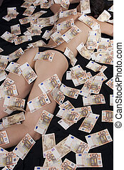 Women covered with banknotes on the bed - A woman lying on...