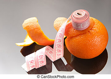 Orange peel and measuring tape on glassy background
