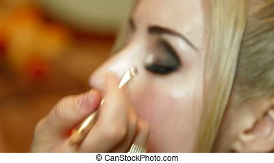 Young Woman Having Mascara Applied - Attractive young woman...