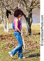 Young woman with a rake in an orchard