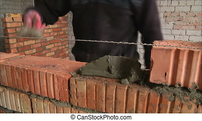 worker builds a wall of bricks