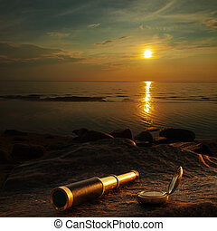 telescope - antique brass telescope and compass at sea coast...