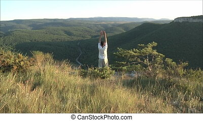 gymnastics in the mountains - man engaged in gymnastics in...