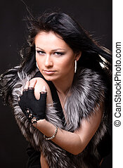 Woman in fur coat on black backgound