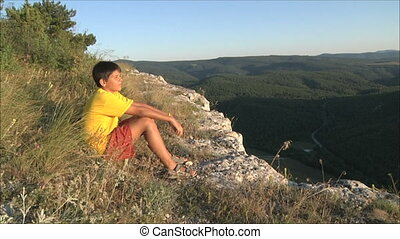 boy is resting in the mountains