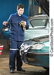 car mechanic inspecting engine oil level - car mechanic...