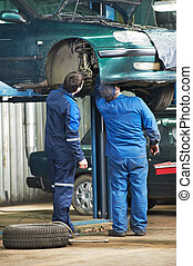 two car mechanic diagnosing auto suspension - two motor...