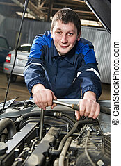 happy automotive mechanic at work with wrench - Smiling...