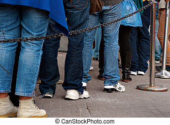 Queue - Legs of persons in casual dresses in queue