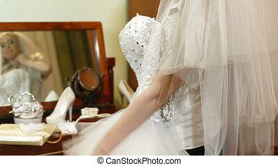 DOLLY: Wedding Dress - Bride trying on a wedding dress near...