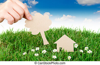 Hand hold paper cut of House over fresh spring green grass -...
