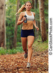 Runner - Young Woman Running on Trail