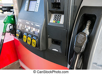Gas pump close up with nozzle in foreground