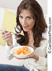 Brunette Woman Eating Melon At Home on Sofa