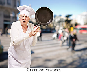 Cook senior woman angry trying to hit with pan at street