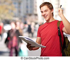 portrait of handsome student holding notebook and pen at...