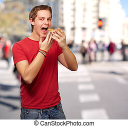 portrait of young man eating pizza at crowded street