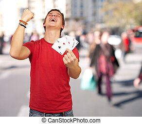 portrait of young man doing a winner gesture playing poker...