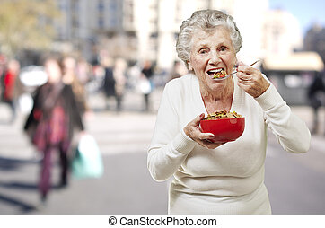 senior woman eating cereals out of a red bowl against a...
