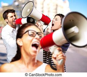jovem, amigos, gritando, megafone, contra, predios