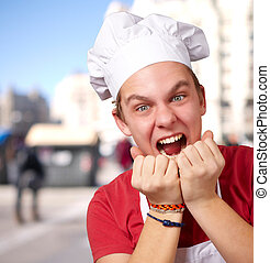 portrait of young cook man screaming at street