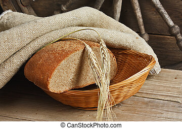 slices of rye bread and ears of corn on a wooden table -...