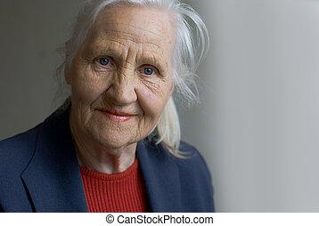 Elderly lady at grey background, indoor