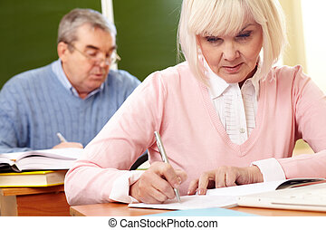 Writing task - Two serious seniors doing a writing task in...