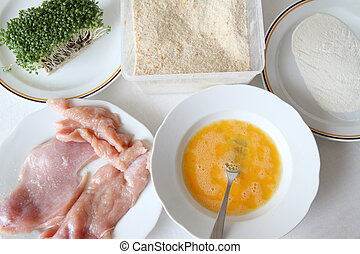 Raw chicken on plate with breadcrumbs, flour, mixed eggs and...