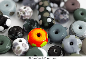 assortment of glass beads with one bright one
